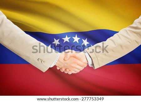 Businessmen shaking hands with flag on background - Venezuela - stock photo