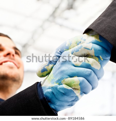 Businessmen shaking world painted hands - stock photo