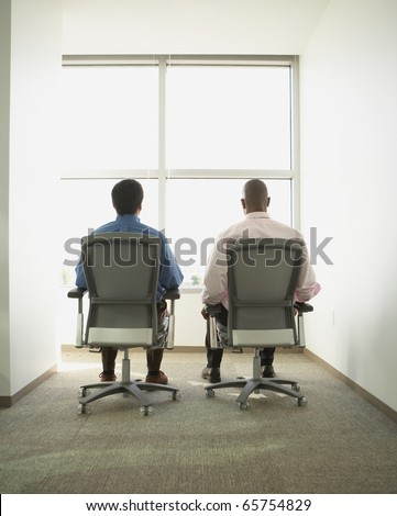 Businessmen sitting in swivel chairs in empty office space