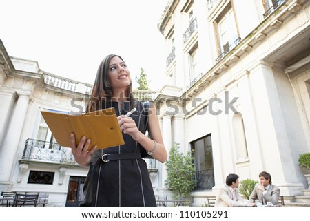Businessmen sitting together while businesswoman writes in a filofax in a coffee terrace set in a colonial building. - stock photo