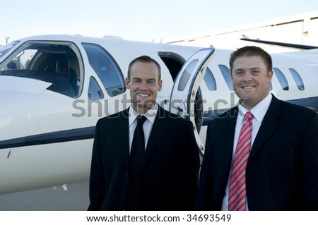 Businessmen smiling in front of their corporate jet - stock photo