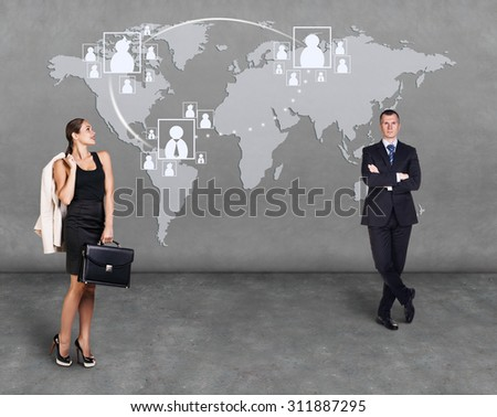 Businessmen standing in front of an earth map. Elements of this image furnished by NASA