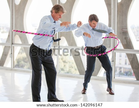 Businessmen taking a play Break hula hooping in a modern office to get ideas flowing