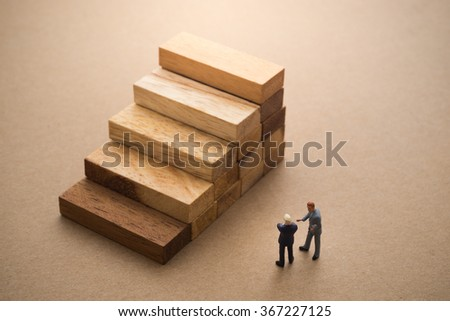Businessmen talking about wood block step, Successive business concept. - stock photo