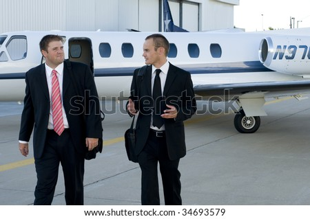 Businessmen talking and walking away from their corporate jet - stock photo