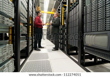 Businessmen talking in a datacenter room - stock photo