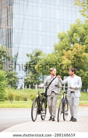 Businessmen talking while walking with bicycles on street - stock photo