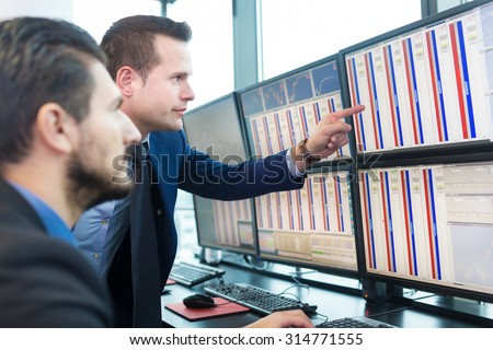 Businessmen trading stocks. Stock traders looking at graphs, indexes and numbers on multiple computer screens. Colleagues in discussion in traders office. Business success concept. - stock photo