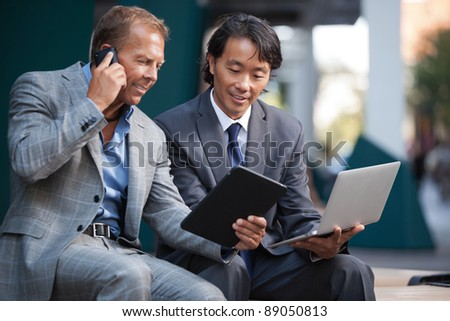 Businessmen using laptop and tablet pc while communication on cell phone - stock photo