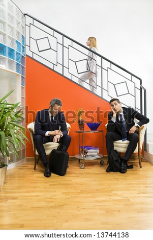 Businessmen waiting in office. Woman stepping up the staircase - stock photo