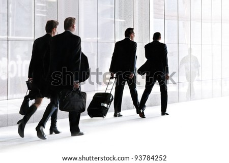 Businessmen walking against the light background of an urban landscape. - stock photo