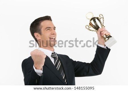Businessmen with business trophy. Cheerful young businessman showing his business trophy and gesturing while isolated on white