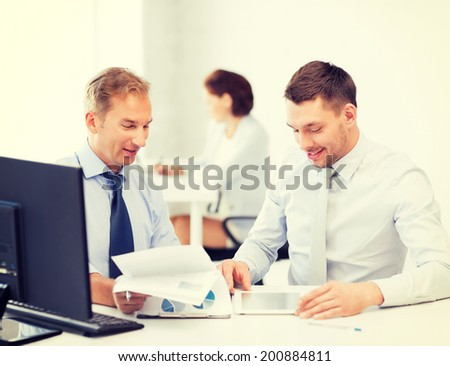 businessmen with notebook and tablet pc discussing graphs on meeting