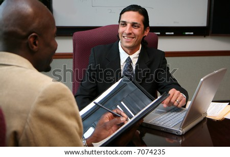 Businessmen working in an office dressed in a suit - stock photo