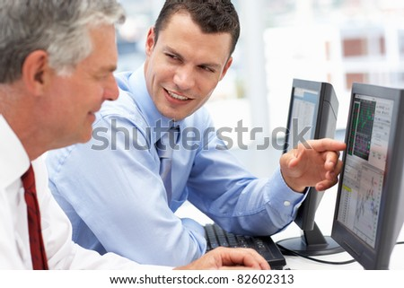 Businessmen working on computers - stock photo