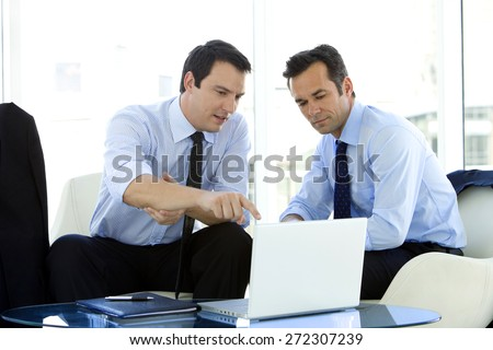 Businessmen working together on laptop in airport lounge - stock photo