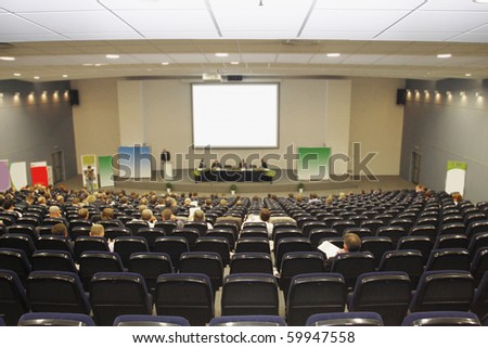 Businessmen works at a conference in big conference hall - stock photo