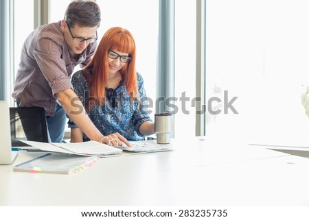 Businesspeople analyzing file together at desk in creative office - stock photo