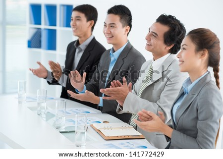 Businesspeople applauding at the end of the conference at the office