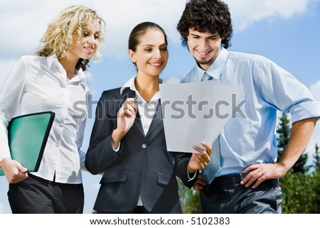 Businesspeople are discussing together a new contract on the street - stock photo