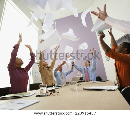 Businesspeople cheering at meeting - stock photo