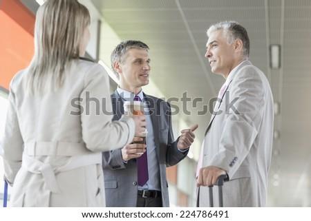 Businesspeople communicating on railroad platform - stock photo