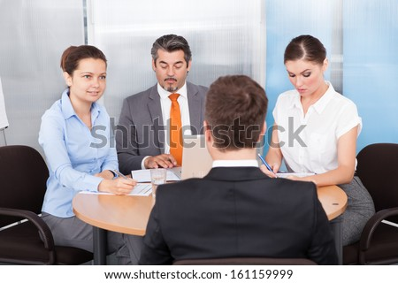 Businesspeople Conducting Interview Of A Candidate In The Office - stock photo