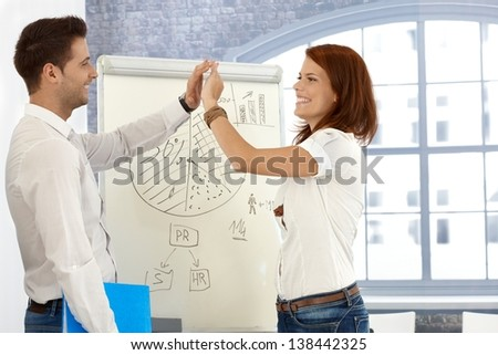 Businesspeople congratulating presentation, clapping high five at whiteboard diagram, laughing. - stock photo