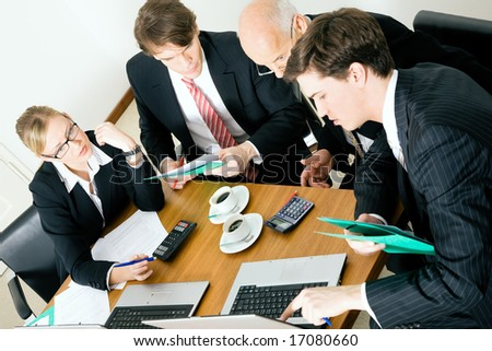 Businesspeople crunching the numbers of a business plan - stock photo