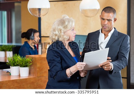 Businesspeople discussing on paperwork while receptionist working at counter in office - stock photo