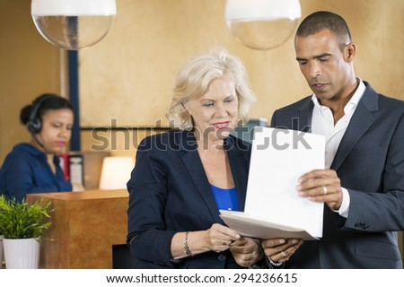 Businesspeople discussing over documents in front of reception desk at office - stock photo