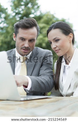 Businesspeople discussing over laptop outdoors - stock photo