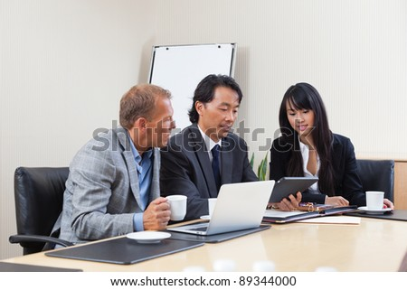 Businesspeople discussing while looking at electronic tablet - stock photo