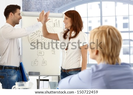 Businesspeople doing high five, after successful presentation in meeting room.