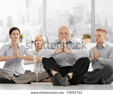 Businesspeople doing meditation in office with closed eyes, hands put together, concentrating.? - stock photo