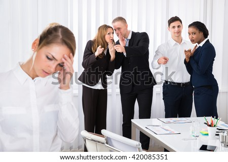Businesspeople Gossiping Behind Stressed Female Colleague In Office - stock photo
