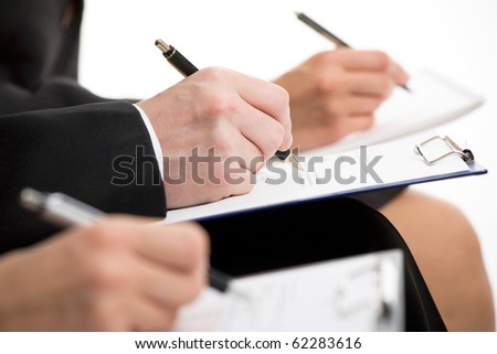 Businesspeople hands over papers making notes at seminar - stock photo