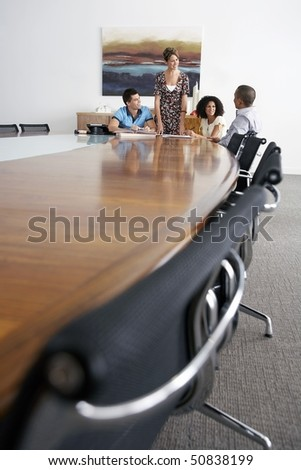 Businesspeople holding a meeting at the end of a conference table - stock photo