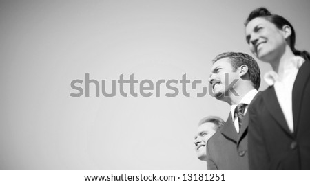 businesspeople in formal wear standing together in line looking in same direction and smiling - stock photo