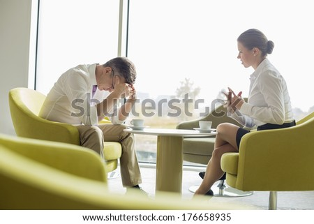 Businesspeople in serious discussion at office lobby - stock photo