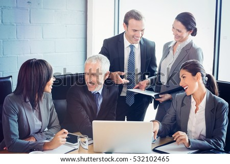 Businesspeople interacting at meeting in conference room together at office