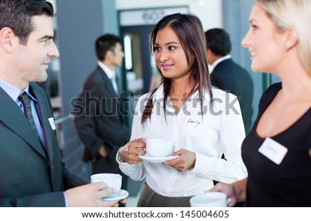 businesspeople interacting during coffee break at business conference - stock photo