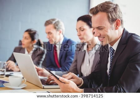 Businesspeople interacting in background and businessman using digital tablet in conference room during meeting