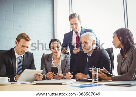 Businesspeople interacting in conference room during meeting