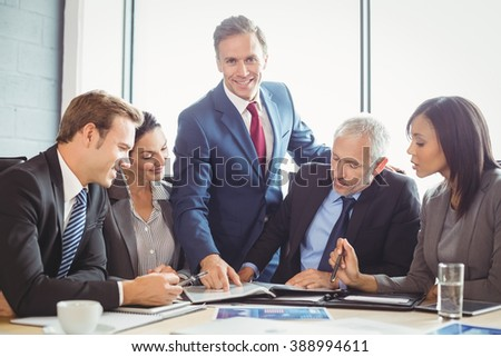 Businesspeople interacting in conference room during meeting - stock photo