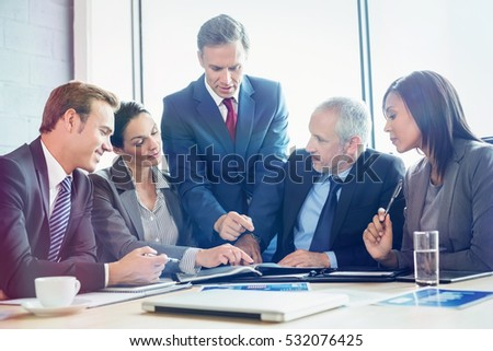 Businesspeople interacting in conference room during meeting at office
