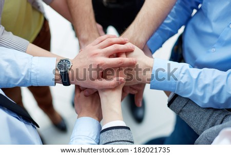 Businesspeople joining their hands in the sign of unity - stock photo