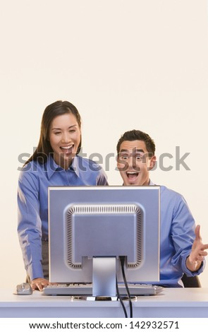 Businesspeople laughing at computer screen