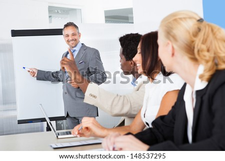 Businesspeople Looking At Businessman Explaining In Presentation