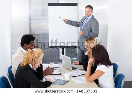 Businesspeople Looking At Businessman Explaining In Presentation - stock photo